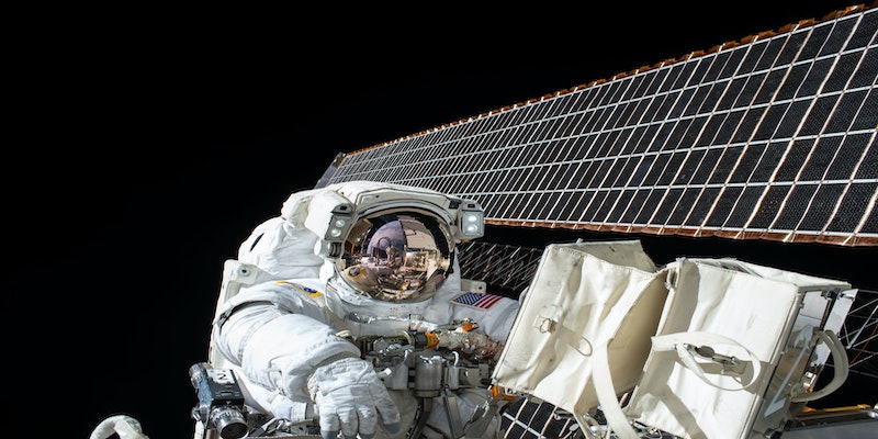 astronaut in space beside satellite